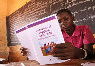 Young Burkina Faso girl reads about menstrual hygiene in school.