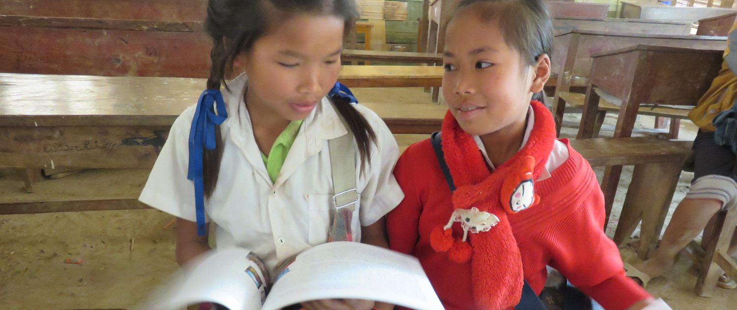 GATE program girl's puberty book being read by two girls in Laos.