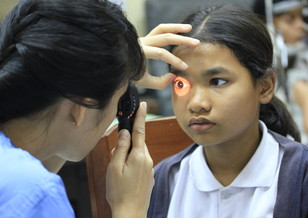 A resident physician examines a child's eye with a direct ophthalmoscope. Photo: Angkor Hospital for Children.