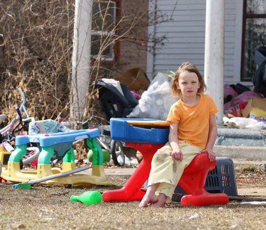 Child in yard with old toys